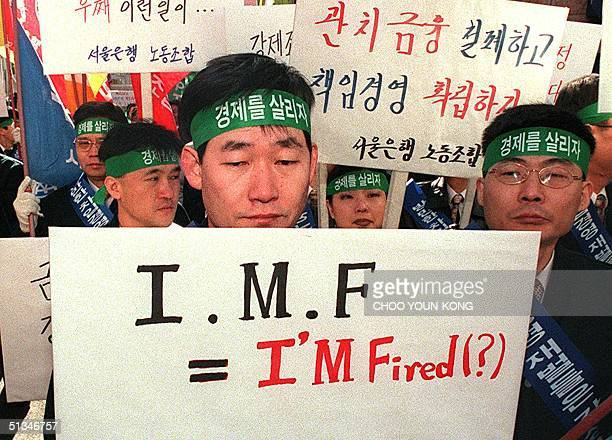 South Korean labor union member of Seoulbank one of South Korea's most baddebt burdened commercial banks looks downcast while holding placard as the...