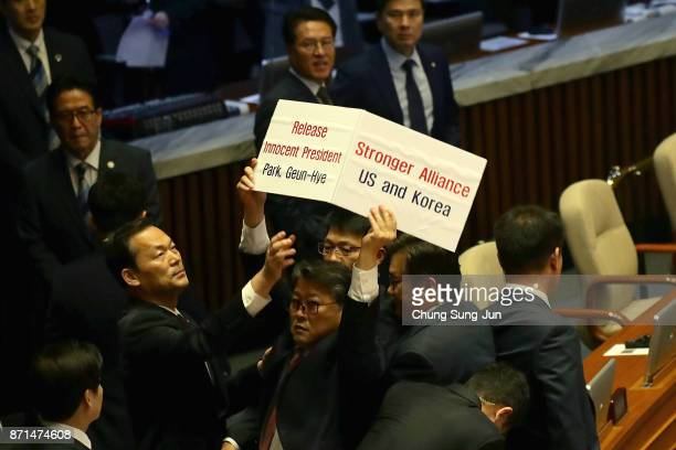 South Korean lawmaker from the Korean Patriots Party Cho Wonjin holds up a sign as security personnel try to block him before the arrival of US...