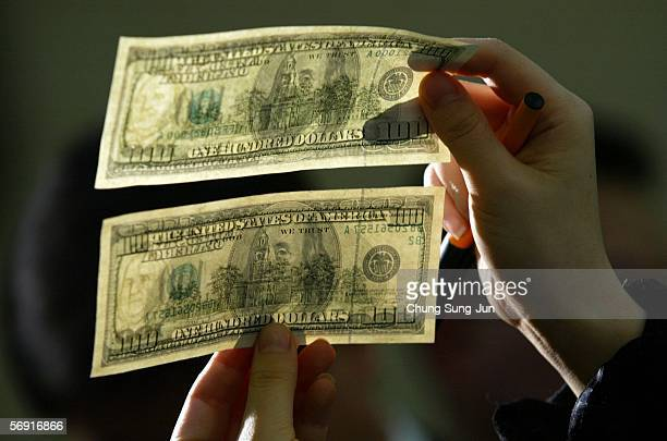 South Korean lawmaker Kim MoonSoo shows a genuine US $100 note above a counterfeit one during a news conference at the National Assembly February 23...