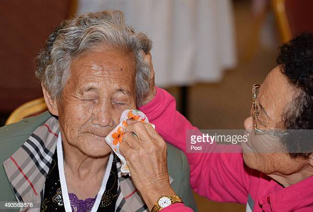 South Korean Lee ChunRan wipes away the tears of her North Korean older sister Ri NanHui during the family reunion after being separated for 60 years...