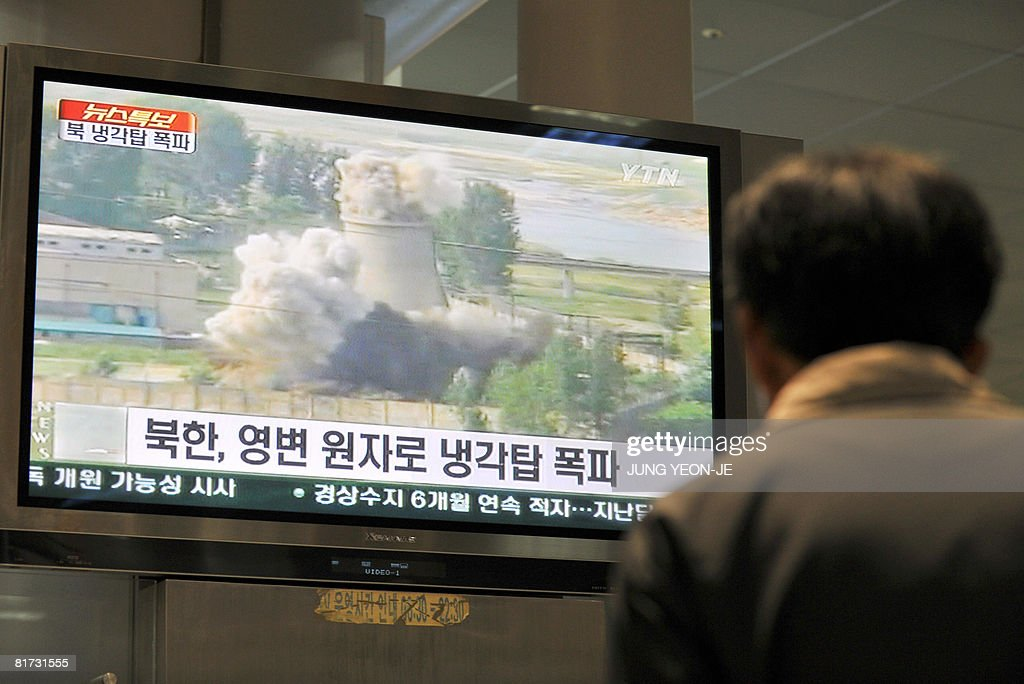 A South Korean looks at a TV screen showing footage of the public demolition of North Korea's cooling tower at its Yongbyon nuclear complex at a...