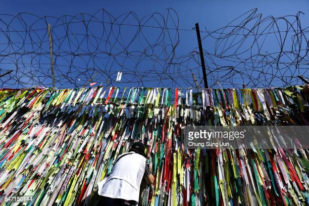South Korean looks over a ribbon wishing for reunification of the two Koreas on the wire fence at the Imjingak Pavilion near the demilitarized zone...