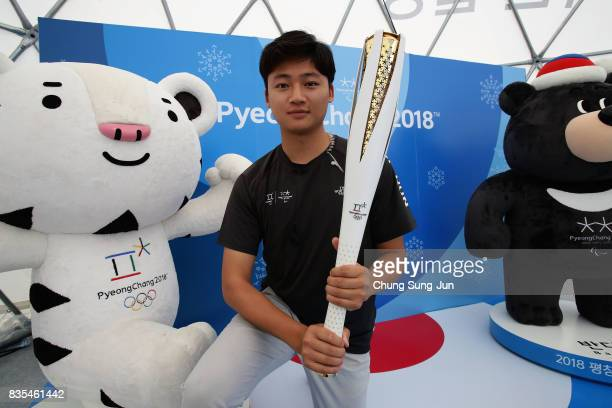 South Korean man holds a PyeongChang Winter Olympics torch at the PR booth next to 'Bobsleigh In the City' event on August 19 2017 in Seoul South...