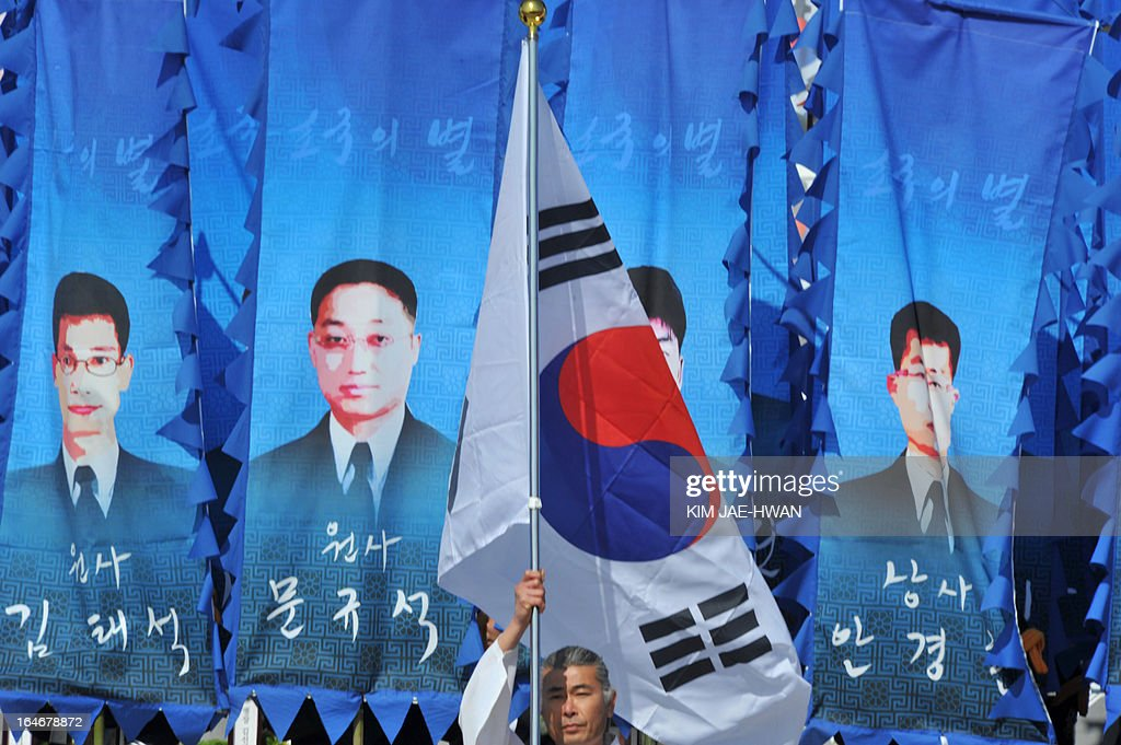 A South Korean man holds up a national flag in front of banners with images of same of the 46 sailors who died in 2010 when the naval vessel 'Cheonan' was sunk, during a ceremony in the central city of Daejeon on March 26, 2013. Forty-six sailors died after the naval vessel Cheonan was sunk by what Seoul insists was a North Korean submarine. Addressing a ceremony for the 46 sailors, South Korean President Park Geun-Hye warned Pyongyang that its only 'path to survival' lay in abandoning its nuclear and missile programs.