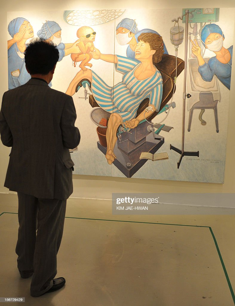 A South Korean man looks at a painting portraying Park Geun-Hye, the presidential candidate of the ruling conservative New Frontier Party, giving birth to her own father and late strongman Park Chung-Hee, at a Seoul gallery on November 20, 2012. South Korea's ruling party has threatened to sue the left-wing artist Hong Sung-Dam who painted its presidential candidate giving birth to her father, former dictator Park Chung-Hee, likening the work to Nazi propaganda.