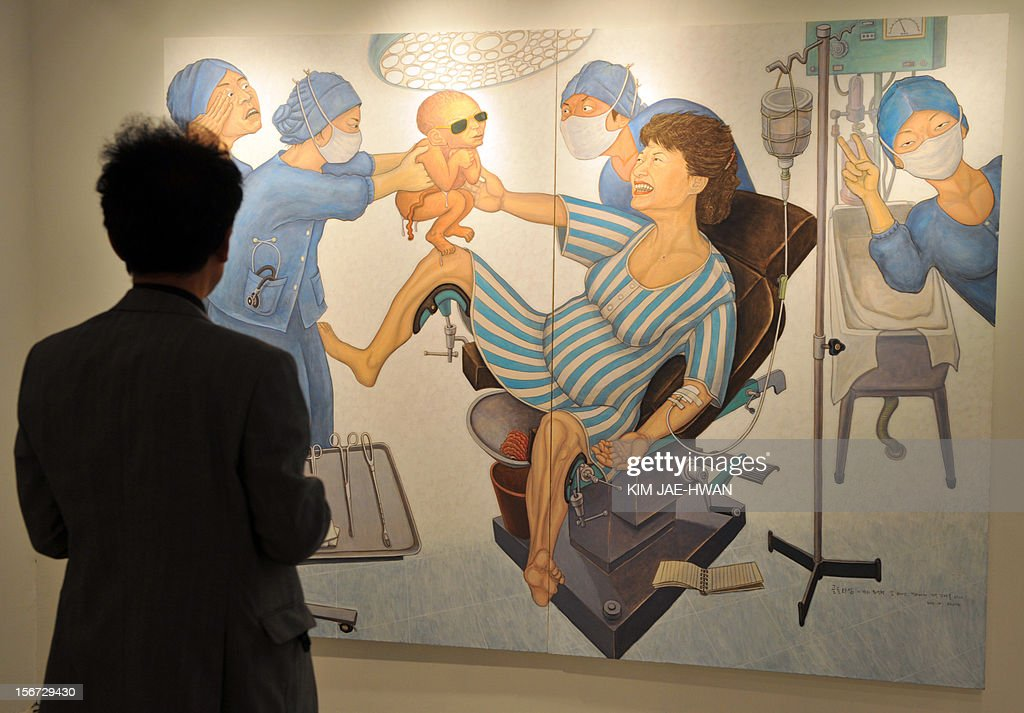 A South Korean man looks at a painting portraying Park Geun-Hye, the presidential candidate of the ruling conservative New Frontier Party, giving birth to her own father and late strongman Park Chung-Hee, at a Seoul gallery on November 20, 2012. South Korea's ruling party has threatened to sue the left-wing artist Hong Sung-Dam who painted its presidential candidate giving birth to her father, former dictator Park Chung-Hee, likening the work to Nazi propaganda. AFP PHOTO / KIM JAE-HWAN CAPTION