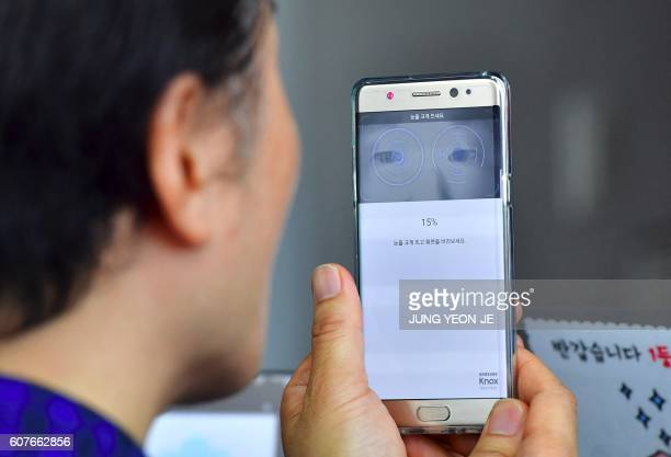 A South Korean man sets up iris recognition function on his replacement Samsung Galaxy Note7 smartphone at a telecommunications shop in Seoul on...