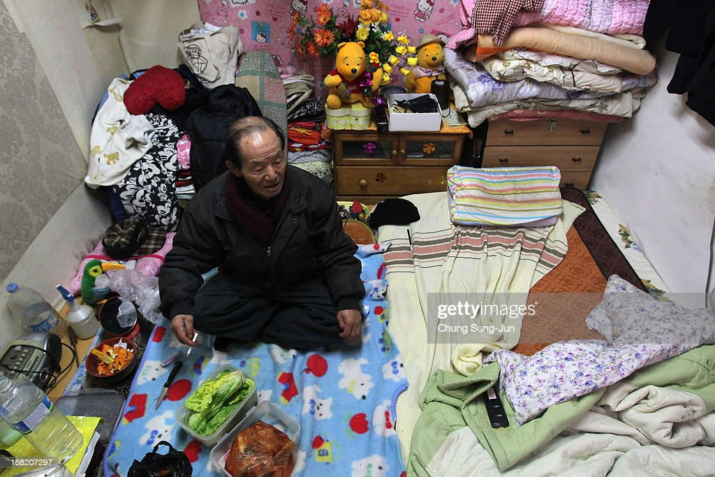 A South Korean man sits in his home in Guryong slum on December 11, 2012 in Seoul, South Korea. Located near South Korea's wealthiest Gangnam district, Guryong slum was established in 1988. With about 3,000 residents, Guryong is now the largest slum settlement in Seoul where most residents are elderly and living in poverty. One of the main South Korean presidential election campaign issues is the economy, as the chaebol, South Korea's business conglomerate, dominates the country's wealth while the economic life of middle class people has not been improving.