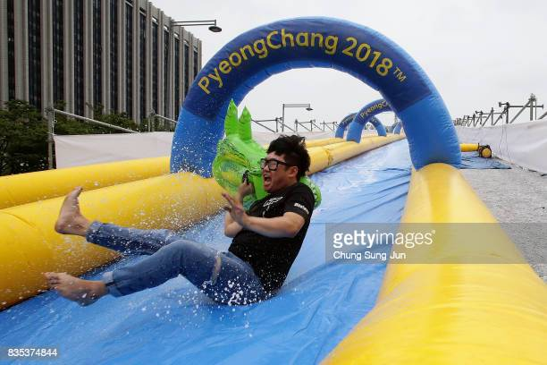 South Korean man slides down on a crocodile shaped inflatable ring during the 'Bobsleigh In the City' on August 19 2017 in Seoul South Korea The...