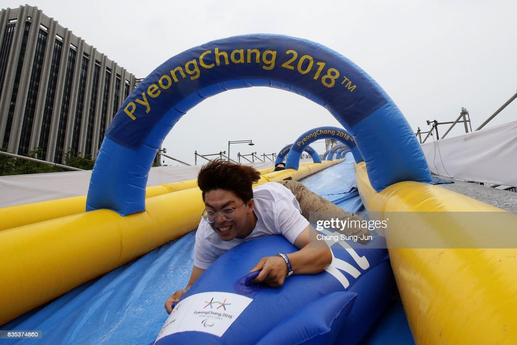 A South Korean man slides down on an inflatable bobsleigh during the 'Bobsleigh In the City' on August 19, 2017 in Seoul, South Korea. The 22-metre-high 300-metre-long water slider has been set up in the central Seoul to promote upcoming PyeongChang Winter Olympics.