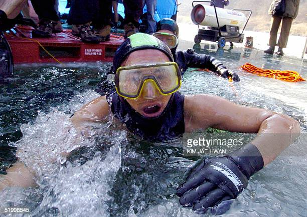 South Korean man wearing goggles swims out of iced water during an icediving contest 16 January 2005 through a hole of the frozen Imjin River at...