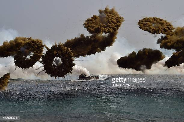 South Korean Marine amphibious assault vehicles fire smoke shells to land on the seashore during a joint landing operation by US and South Korean...
