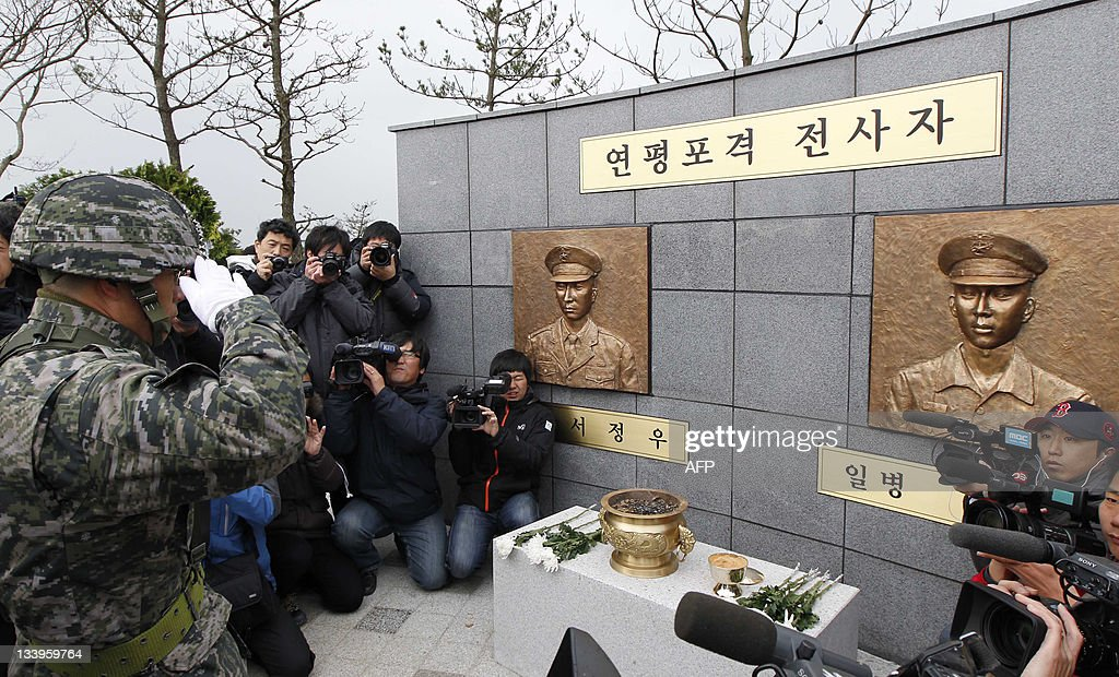 A South Korean Marine officer salutes bronze statues of two marines that were put up during a ceremony to mark the first anniversary of North Korea's...