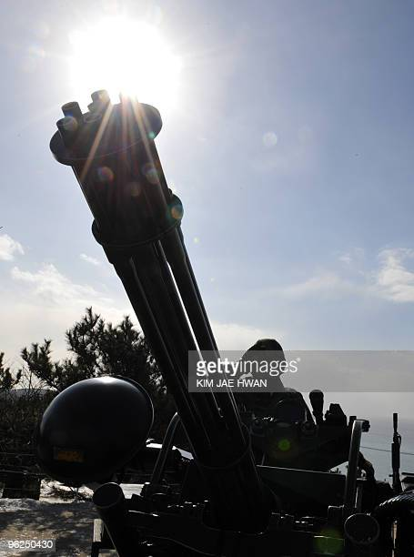 A South Korean marine stands guard at an antiaircraft gun position on Yeonpyeong Island in the disputed waters of the Yellow Sea on January 29 2010...