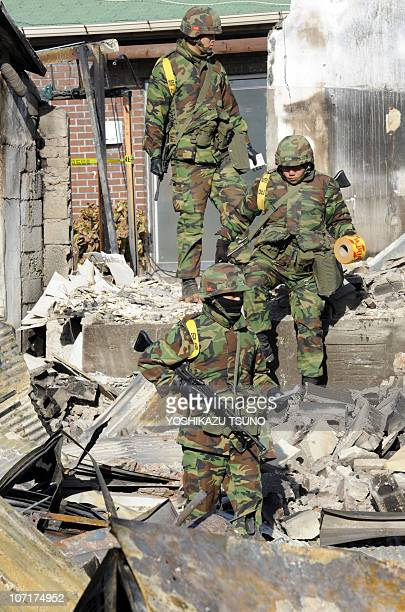 South Korean Marines climp over debris as they patrol a damaged area on Yeonpyeong island on November 28 2010 five days after the North stunned the...