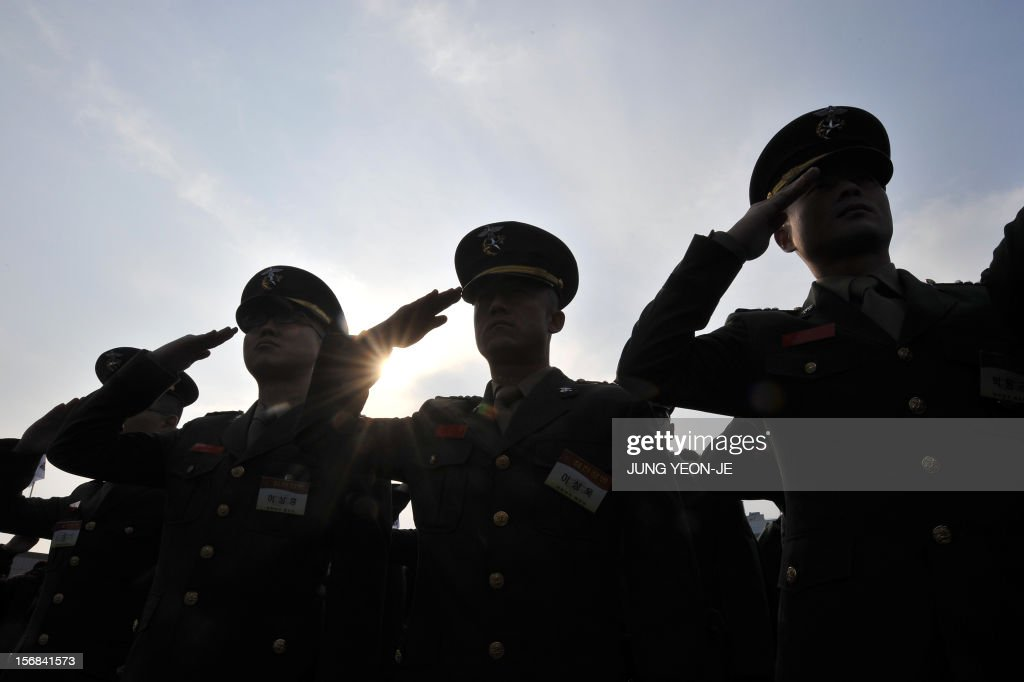 South Korean marines salute during a ceremony to commemorate the second anniversary of North Korea's shelling of Yeonpyeong Island at the War Memorial in Seoul on November 23, 2012. The November 23, 2010 attack on Yeonpyeong island killed two South Korean marines and two civilians in one of the most serious border incidents since the 1950-1953 Korean War.