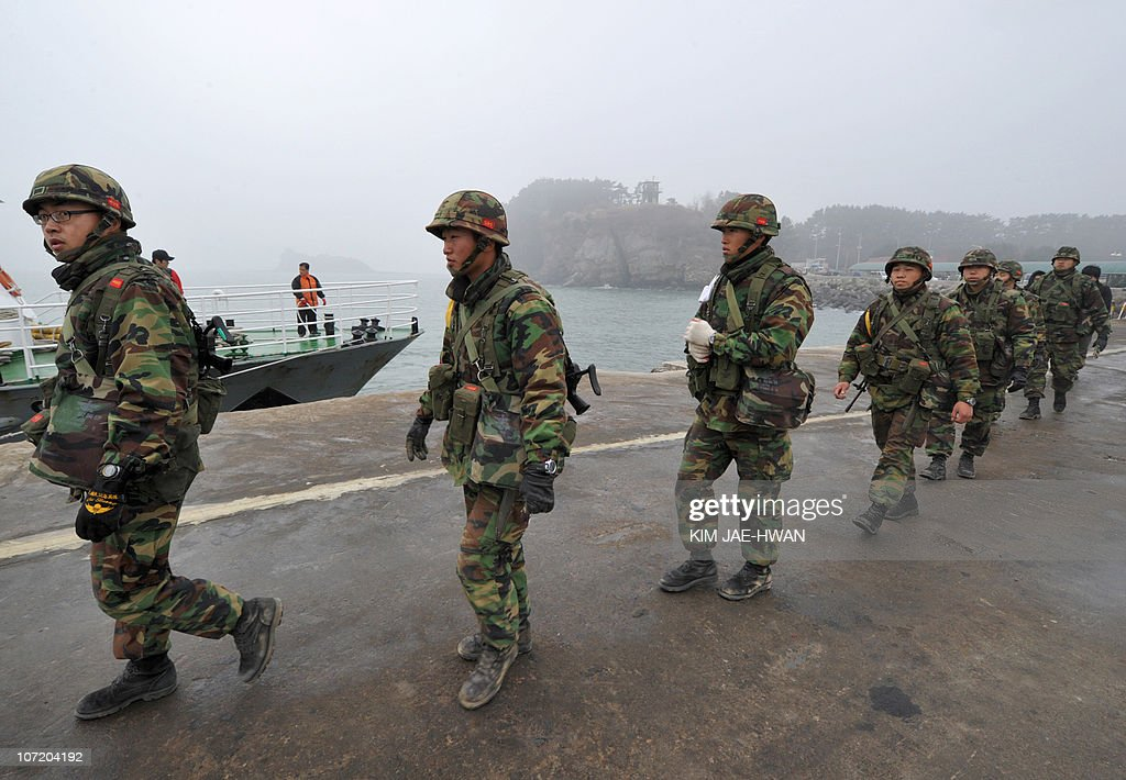 South Korean Marines walk along the pier at Yeonpyeong island on November 30 2010 South Korea deployed rocket launchers and extra artillery on a...