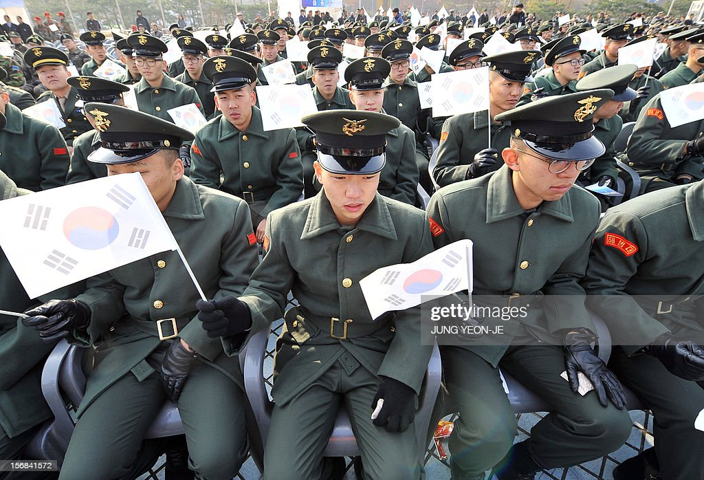 South Korean marines wave national flags during a ceremony to commemorate the second anniversary of North Korea's 2010 shelling of Yeonpyeong Island at the War Memorial in Seoul on November 23, 2012. The November 23, 2010 attack on Yeonpyeong island killed two South Korean marines and two civilians in one of the most serious border incidents since the 1950-1953 Korean War. AFP PHOTO / JUNG YEON-JE