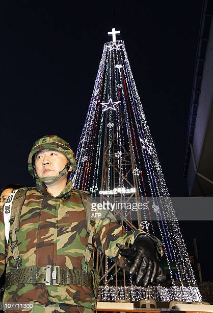 A South Korean military officer stands guard as Christians prepare a lighting ceremony in front of a Christmas tree atop a militarycontrolled hill...