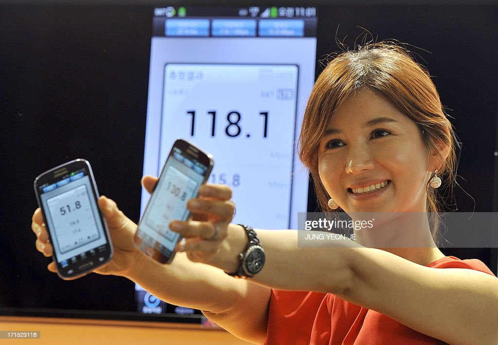 A South Korean model shows Galaxy S4 smartphones displaying wireless data speed via SK Telecom's new mobile network, LTE-Advanced, in Seoul on June 26, 2013. South Korea's SK Telecom announced on June 26 the launch of a new generation mobile network that offers speeds twice that of its existing long term evolution (LTE) network and 10 times that of 3G services.