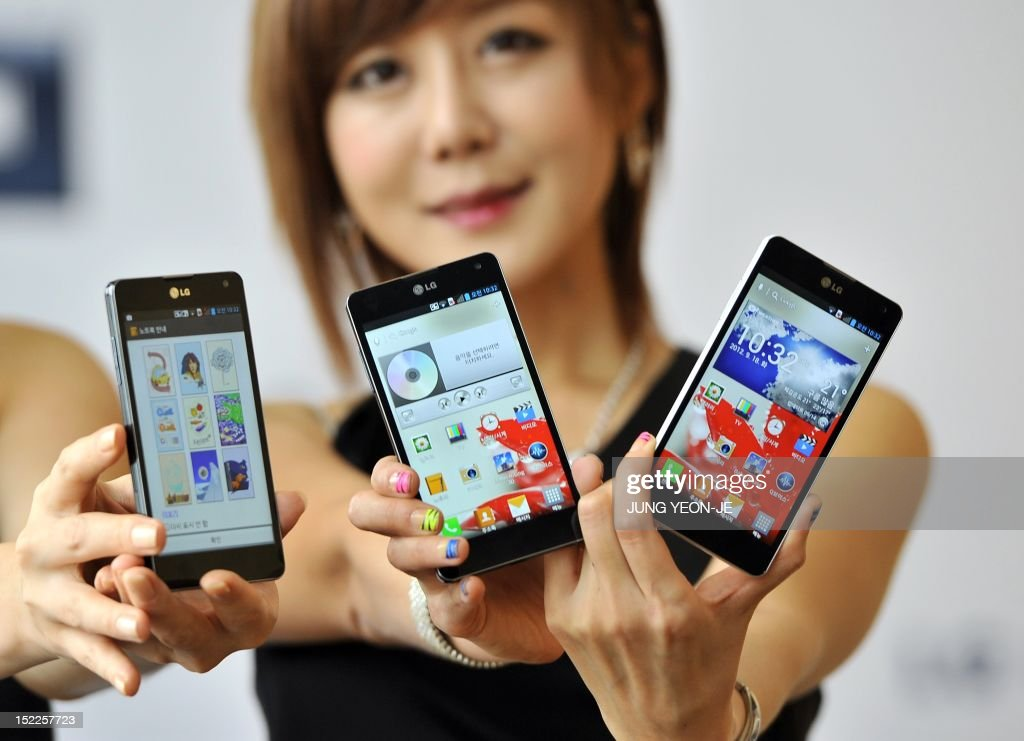 South Korean models display LG's new smartphone 'Optimus G' equipped with quadcore chipset during a launch ceremony in Seoul on Spetember 18, 2012. LG Electronics launched its new flagship smartphone aimed to capture a bigger stake in the global market amid a recent flurry of new products from rivals including Apple and Samsung Electronics.