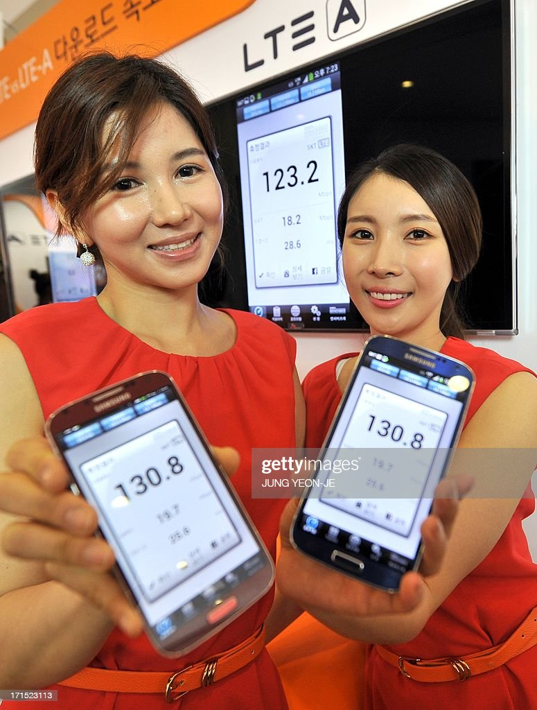 South Korean models show Galaxy S4 smartphones displaying wireless data speed via SK Telecom's new mobile network, LTE-Advanced, in Seoul on June 26, 2013. South Korea's SK Telecom announced on June 26 the launch of a new generation mobile network that offers speeds twice that of its existing long term evolution (LTE) network and 10 times that of 3G services.