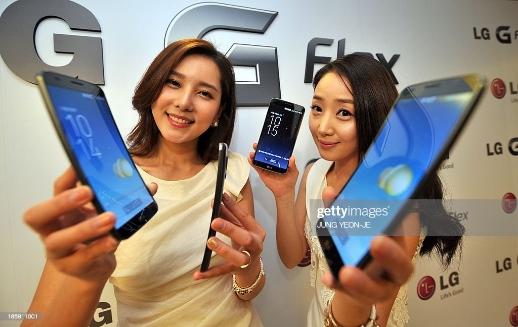 South Korean models show LG Electronics' curved-screen smartphone 'G Flex' during a media event to unveil the new product at the company's headquarters in Seoul on November 5, 2013. The G Flex has a 6-inch plastic OLED display that curves inward from top and bottom. The device will hit the market in South Korea next week. AFP PHOTO / JUNG YEON-JE
