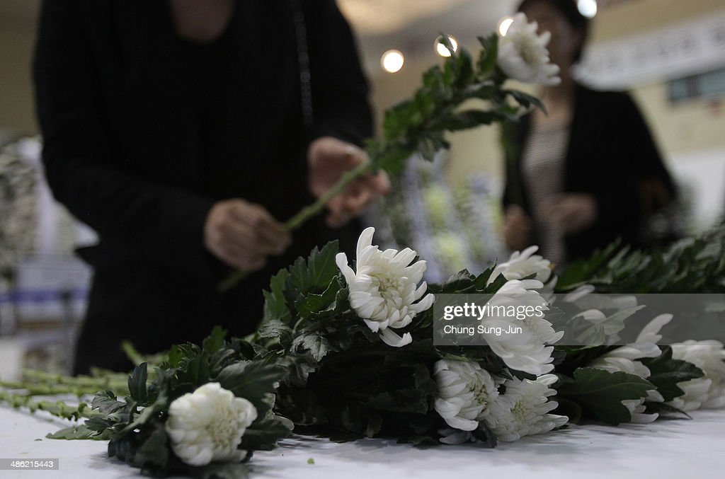 South Korean mouners pay a tribute at a group memorial altar for victims of sunken passengers ship at the Ansan Olympic Memorial Hall on April 23, 2014 in Ansan, South Korea. At the altar, Friends and relatives are able to pay tribute to those who have passed in the April 16 ferry disaster off of Jindo Island in South Korea. The confirmed death toll now reached 130, and more than 170 people are still missing, as reported.