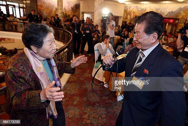 South Korean Nam JoongRang sings with her North Korean cousin at the group luncheon meeting after being separated for 60 years during the family...
