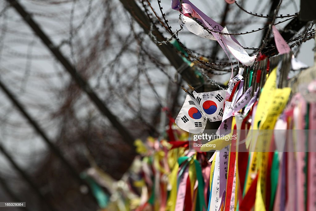 South Korean national flags and ribbons hang on a barbed-wire fence at the Imjingak pavilion near the demilitarized zone (DMZ) in Paju, South Korea, on Wednesday, April 3, 2013. North Korea prevented South Korean workers from entering a jointly run industrial park today, adding to tensions after saying it will restart a mothballed nuclear plant and threatening to attack its southern neighbor. Photographer: SeongJoon Cho/Bloomberg via Getty Images