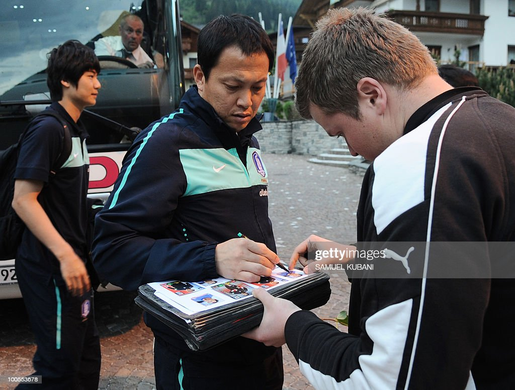South Korean national football player Lee Woon Jae (C) gives his autograph as he gets out of a bus during the his team arrival for their training camp in Tirolian village of Neustift im Stubaital in Austria on May 25, 2010, prior to the FIFA World cup 2010 in South Africa.