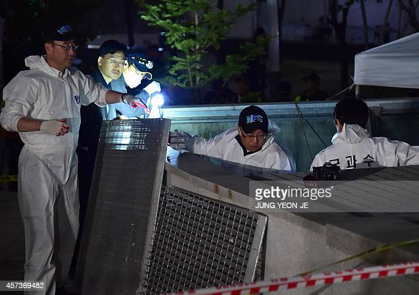 South Korean National Forensic Service members check a broken ventilation grate after concert goers fell through it into an underground parking area...