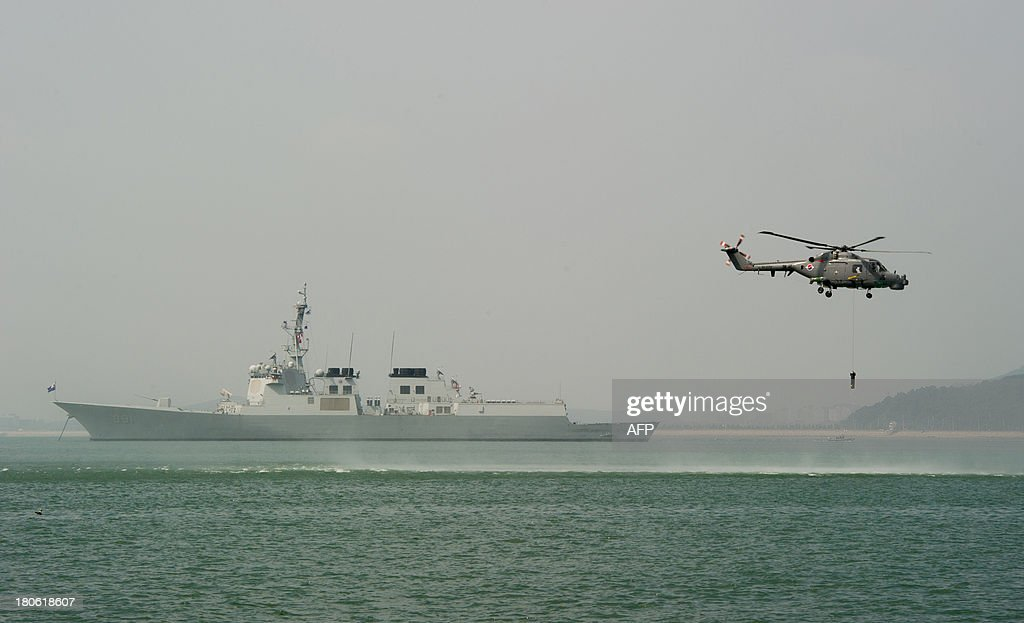 A South Korean Navy Lynx anti-submarine helicoptor (R) lowers its sonar buoy to search for enemy subs near Wolmi island (Wolmido) at Incheon on September 15, 2013 during a re-enactment of the landing at Incheon to mark the 63th anniversary of the start of Operation Chromite, the battle that turned the tide in the Korean War. The exercise marked the 63th anniversary of the daring Incheon Landing which was led by US General Douglas MacArthur and led two weeks later to the recapture of Seoul from North Korean invaders.