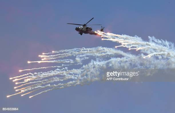 A South Korean Navy Lynx helicopter fires flares during a commemoration ceremony marking South Korea's Armed Forces Day which will fall on October 1...