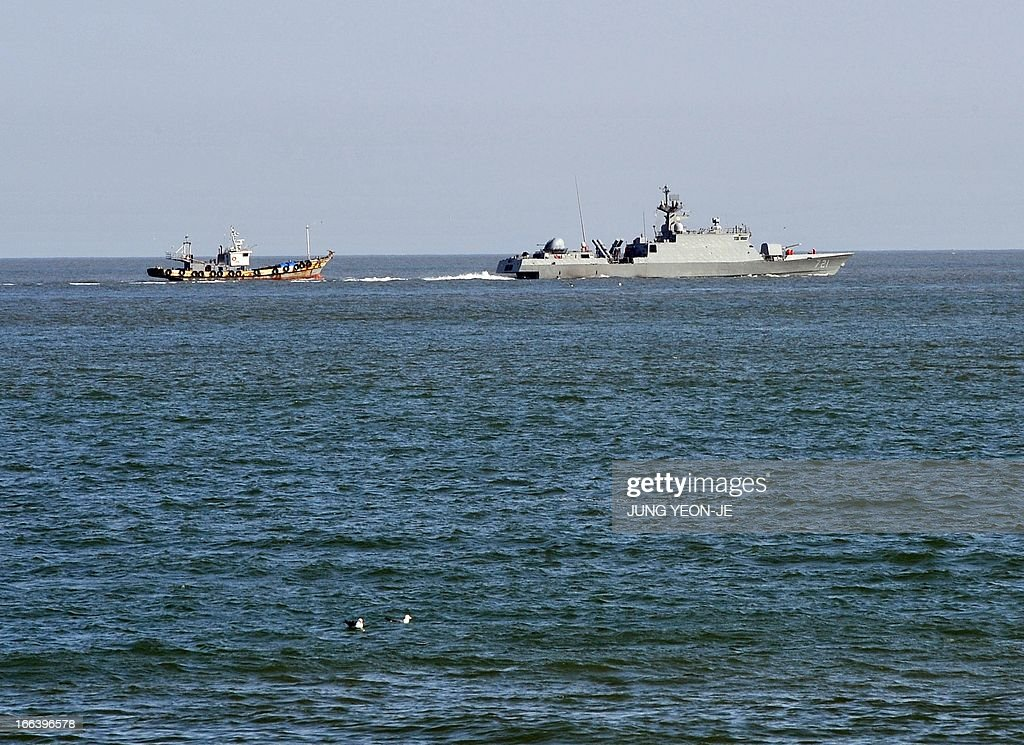 A South Korean Navy vessel sails by a fishing boat off the South Koreacontrolled island of Yeonpyeong near the disputed waters of the Yellow Sea on...