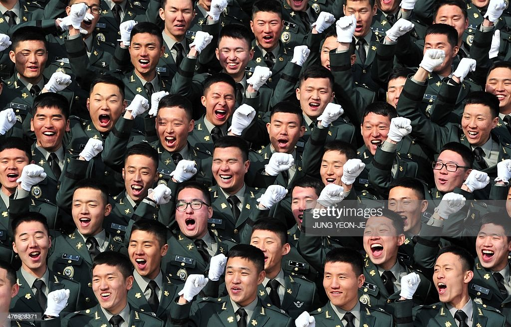 South Korean new military officers cheer during the joint commission ceremony of 5,860 new officers of the army, navy, air force and marines at the military headquarters in Gyeryong, south of Seoul, on March 6, 2014. South Korean President Park Geun-Hye urged North Korea to give up its nuclear program, saying denuclearization will pave the way for greater economic cooperation and ultimately unification between the two divided states. AFP PHOTO / POOL / JUNG YEON-JE