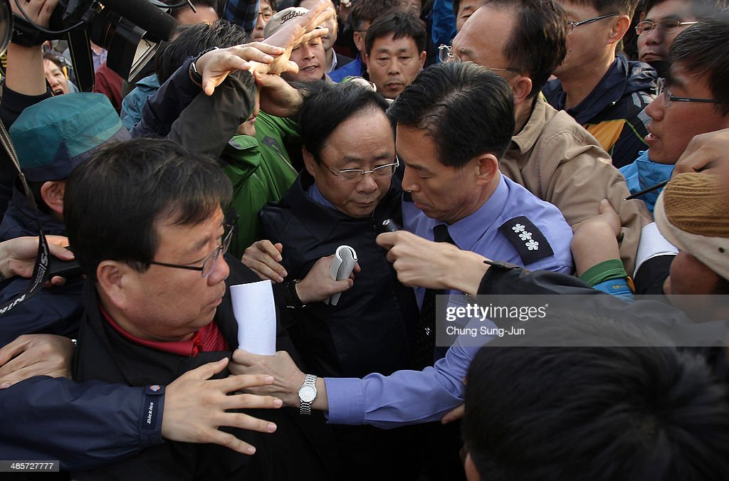 South Korean Ocean and Fisheries Minister Lee Ju-Young is surrounded by relatives of missing passengers of a sunken ferry as he visit a Jindo port on April 20, 2014 in Jindo-gun, South Korea. At least fifty eight people are reported dead, with 244 still missing. The ferry identified as the Sewol was carrying about 470 passengers, including the students and teachers, traveling to Jeju Island.