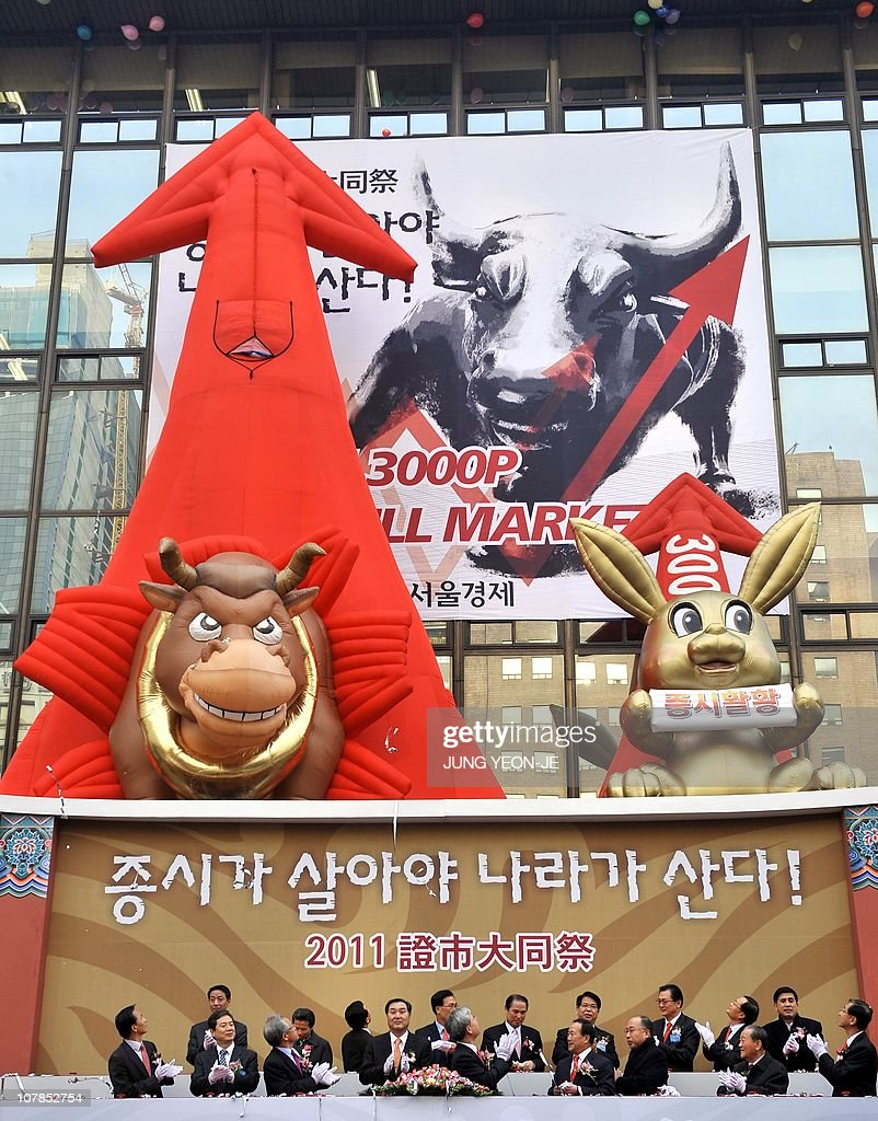 South Korean officers celebrate under a large bull and a rabbit to illustrate their desire for a bullish market in the Year of the Rabbit during the...