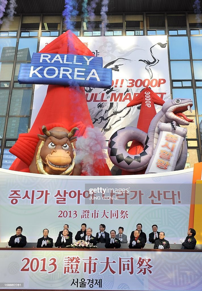 South Korean officers (bottom) celebrate under balloons of a large bull (L) and a snake (R) to illustrate their desire for a bullish market in the Chinese lunar year of the Snake, during the New Year opening of the stock market at the Korea Exchange in Seoul on January 2, 2013. The benchmark Korea Composite Stock Price Index (KOSPI) gained 15.5 points, or 0.78 percent, to 2,012.55 in the first 15 minutes of trading. AFP PHOTO / JUNG YEON-JE