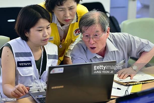 South Korean officials help an elderly man who was separated from his families during the Korean War to check applications for an interKorean family...