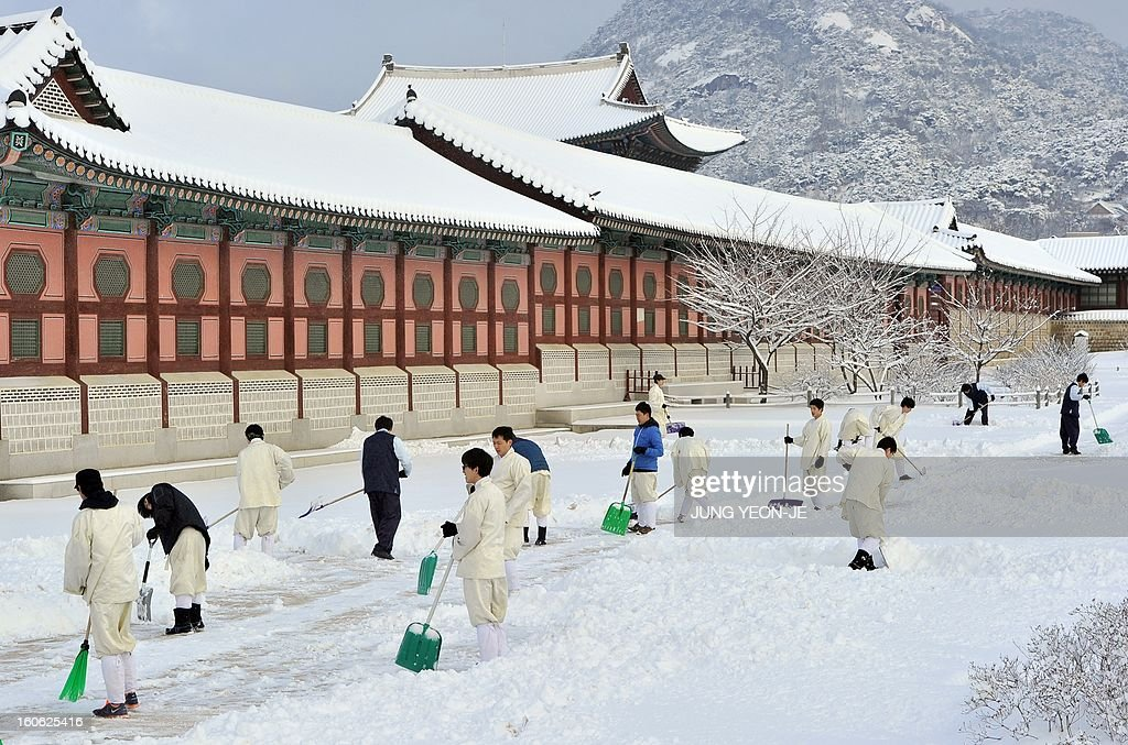 South Korean officials remove snow at the Gyeogbok palace in downtown Seoul on February 4, 2013. Heavy snow pounded central South Korea, including the capital city of Seoul, on February 4, disrupting air and ground traffic and delaying the start of the school day. AFP PHOTO / JUNG YEON-JE