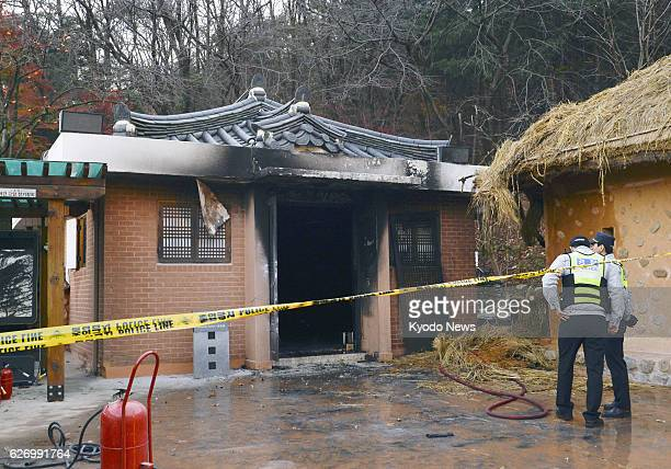 South Korean officials stand by the partly burned birthplace of the late President Park Chung Hee the father of President Park Geun Hye in Gumi...