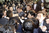South Korean opposition party legislators scuffle with ruling party legislators outside a parliamentary committee room in Seoul on December 18 2008 A...
