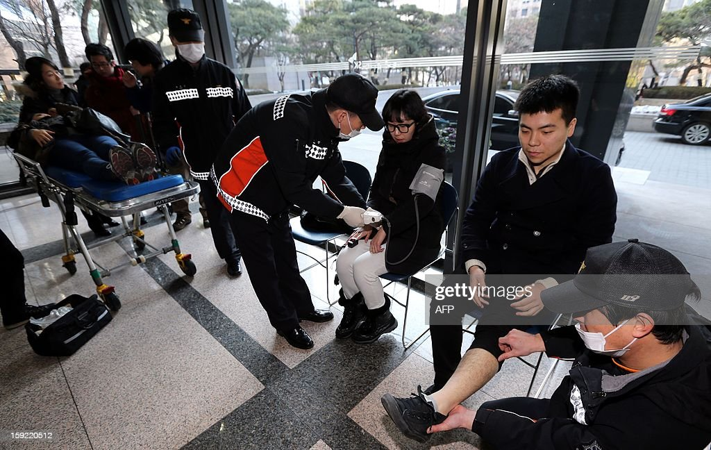 South Korean paramedics give first aid to mock injured persons during a national drill in the case of an emergency power blackout in Seoul on January 10, 2013. Sirens sounded across South Korea and subway systems grounded to a halt as the government held a national drill aimed at averting a countrywide power blackout. REPUBLIC