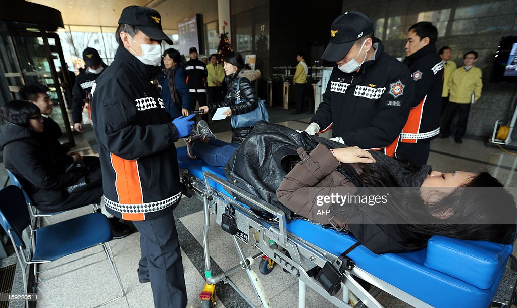 South Korean paramedics move a mock injured person (R) during a national drill in the case of an emergency power blackout in Seoul on January 10, 2013. Sirens sounded across South Korea and subway systems grounded to a halt as the government held a national drill aimed at averting a countrywide power blackout. REPUBLIC OF KOREA OUT AFP PHOTO/DONG-A ILBO