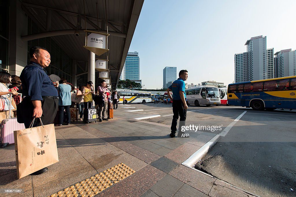 South Korean passengers and a bus operator (C) wait for buses at a bus terminal in Seoul on September 17, 2013 ahead of Chuseok, South Korea's biggest holiday, which lasts from September 18-20. Approximately thirty five million people are expected to travel to their home towns and villages across the country to visit relatives this year, an increase of 4.9 percent compared with last year's holiday. AFP PHOTO / KIM DOO-HO