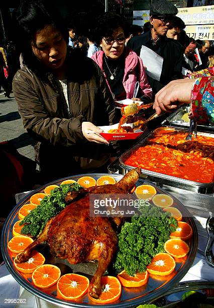 South Korean pedestrians get free chicken and duck meals during a campaign to promote chicken and duck meat on a street Febuary 19 2004 in Seoul...