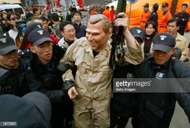 South Korean police arrest a peace activist wearing a mask of US President George W Bush and brandishing a fake M16 assault riffle after the activist...