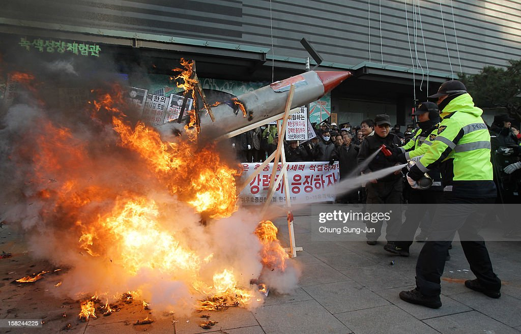 South Korean police extinguish flames after protesters burned a mock up of North Korea's missile and portraits of North Korean leader Kim Jong-Un during an anti-North Korea rally demonstrating against North Korea having launched a long-range missile on December 12, 2012 in Seoul, South Korea. North Korea launched a long range missile on 9:49am local time.
