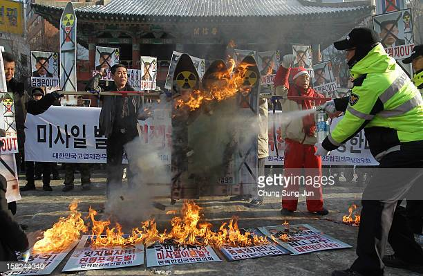 South Korean police extinguish flames after protesters burned a mock up of North Korea's missile and portraits of North Korean leader Kim JongUn...